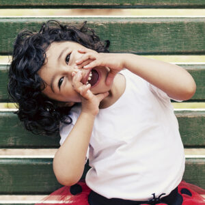 Toddler girl sitting on park bench making a face
